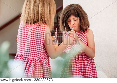 Two Little Girls Drinking Fruit Juices. Brunette Girl Trying The One From The Other Girl