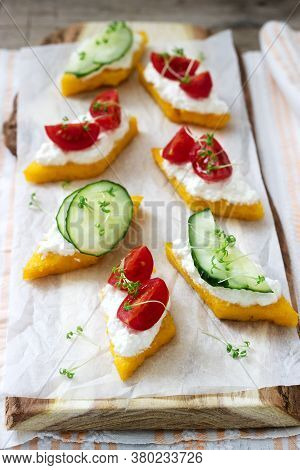 Vegetarian Canapes From Polenta With Cheese, Vegetables And Cress On A Light Background. Rustic Styl