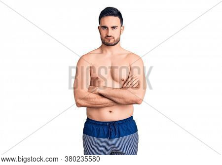 Young handsome man wearing swimwear skeptic and nervous, disapproving expression on face with crossed arms. negative person.