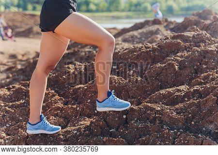 Woman Runner Legs Running On Mountain Trail. Feet Of Woman Runner Running Over Stones On Mountain Tr