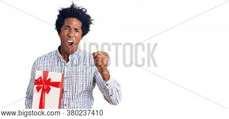 Handsome african american man with afro hair holding gift annoyed and frustrated shouting with anger, yelling crazy with anger and hand raised
