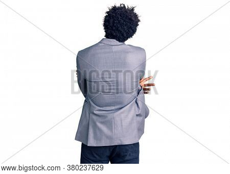 Handsome african american man with afro hair wearing business jacket hugging oneself happy and positive from backwards. self love and self care