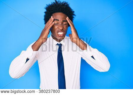 Handsome african american man with afro hair wearing business shirt and tie with hand on head, headache because stress. suffering migraine.