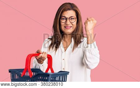 Middle age latin woman holding supermarket shopping basket annoyed and frustrated shouting with anger, yelling crazy with anger and hand raised