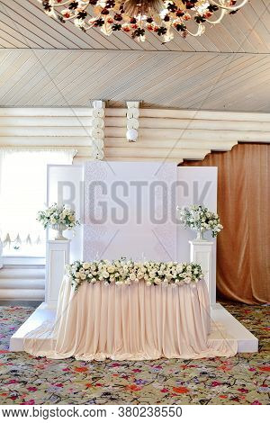 Wedding Presidium In Restaurant, Free Space. Wedding Banquet Table For Newlyweds With Flowers, Green