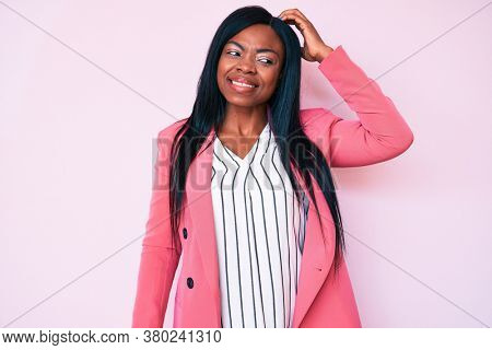 Young african american woman wearing business clothes confuse and wonder about question. uncertain with doubt, thinking with hand on head. pensive concept.