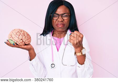 Young african american woman wearing doctor coat holding brain annoyed and frustrated shouting with anger, yelling crazy with anger and hand raised