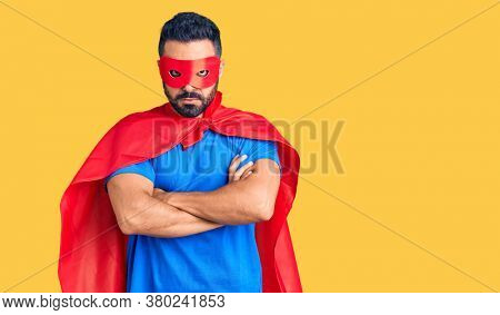 Young hispanic man wearing super hero costume skeptic and nervous, disapproving expression on face with crossed arms. negative person.