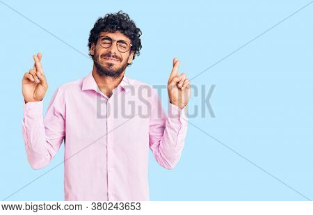 Handsome young man with curly hair and bear wearing business clothes gesturing finger crossed smiling with hope and eyes closed. luck and superstitious concept.