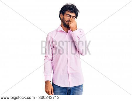 Handsome young man with curly hair and bear wearing business clothes smelling something stinky and disgusting, intolerable smell, holding breath with fingers on nose. bad smell