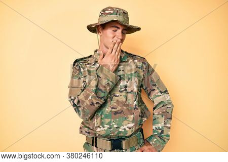 Young handsome man wearing camouflage army uniform bored yawning tired covering mouth with hand. restless and sleepiness.
