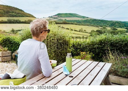 Backview Young Man Sitting Behind A Wooden Table And Enjoying Beautiful Local Nature View With Tea T