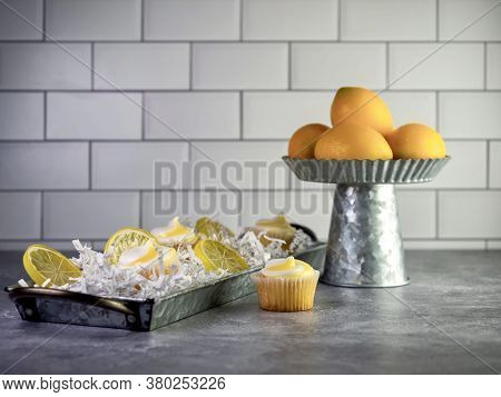 Mini Lemon Cupcakes With White And Yellow Swirled Frosting Sitting In A Metal Tray Garnished With Ar