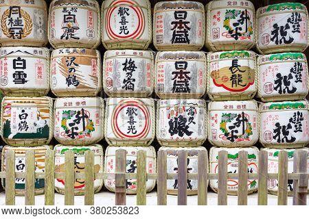 Nara, Japan - 13 June 2016: Traditional colourful barrels of sake with japanese signs atNara Park. Called kazaridaru, these are displayed outside of Shinto shrines.