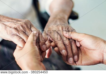 Close up hands of helping hands elderly home care.