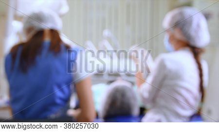 Young woman at dental clinic. Female dentist with assistant treating cavities in a patient mouth in modern dental office. Handheld shot with gimbal. Out of focus for background use.
