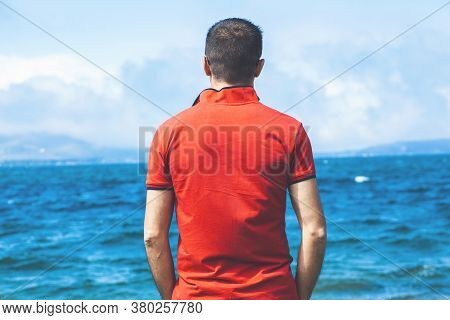 Rear View Of Young Male Traveler In Shirt And Shorts Standing By The Sea And Enjoying Nature And Sec