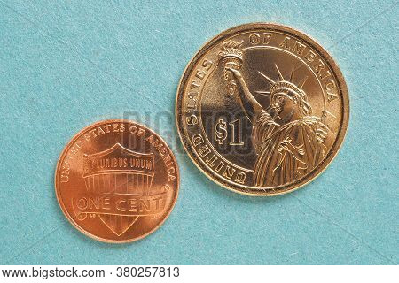 Us American Coins Lie On A Light Blue Cardboard Background. Denomination: 1 Dollar And 1 Cent. Rever