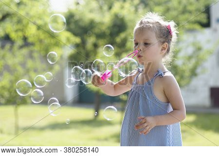 Cute Little Girl Is Blowing Soap Bubbles With Pink Bubble Wand Outdoors.