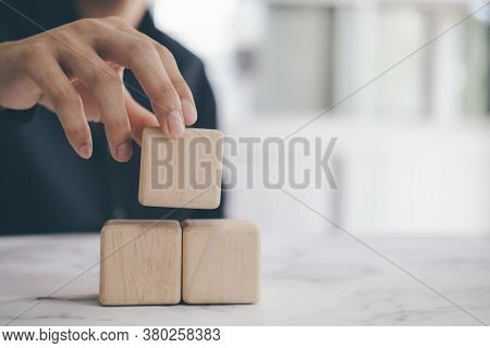 Hand Holding Blank Wood Cube Block On Top Pyramid