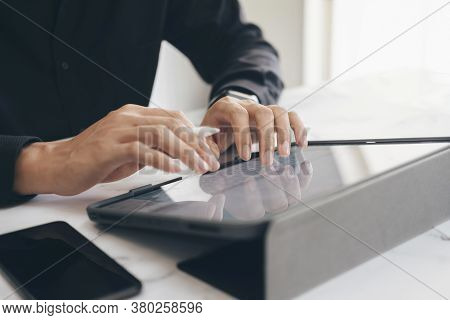Close-up Of Young Businessman Hands Working With Tablet
