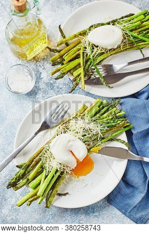 Green Asparagus With Poached Egg And Parmesan, Vegetarian Breakfast Served On Two White Plate On Lig
