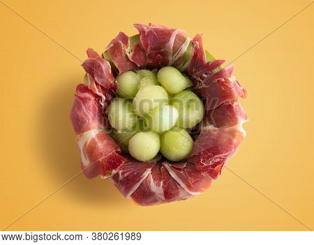 Melon With Air Dried Ham, Served In Halved Melon Stuffed With Serrano Ham And Melon Balls. Isolated