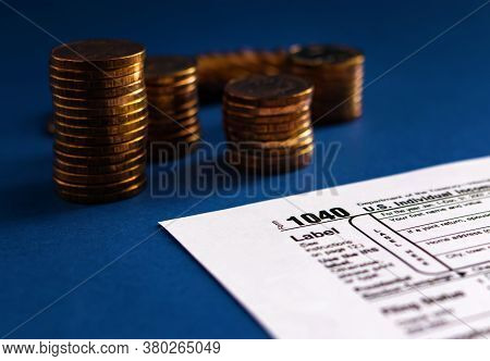 Tax Form 1040 And Stacks Of Coins On A Blue Background. Concept Of Taxation And Business