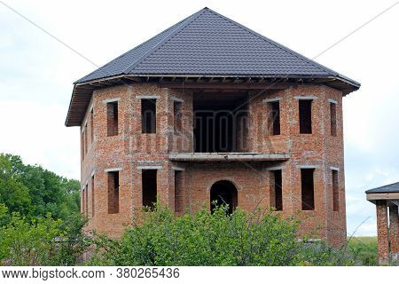 Facade Of An Unfinished Twostory House With No Red Brick Windows. Large House With Rounded Corners A