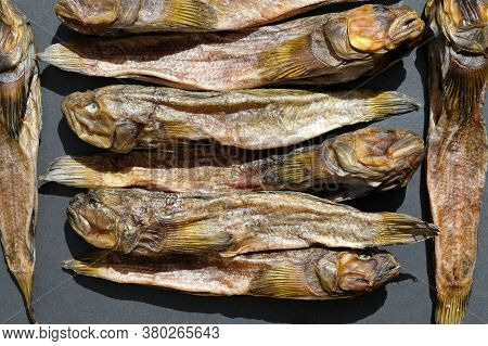 Dried Gobies On A Black Board Top View. Salted Dried Fish For Beer. Dried Gobies