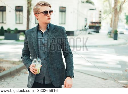 Photo Of Young Handsome Man Croosing Street With Limonade In Hand
