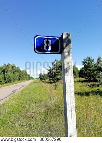 Kilometer Sign With The Number 8 On The Post Of A Rural Road In Summer. Curb, Road Signs