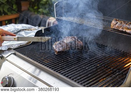 Man Cooking Beef On The Grill Outside, Flipping The Meat With Tongs.