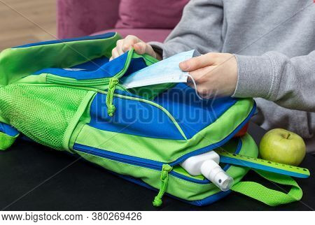 Boy Puts Protective Mask And Hands Sanitizer Spray To His School Bag. Back To School 2020 After Quar