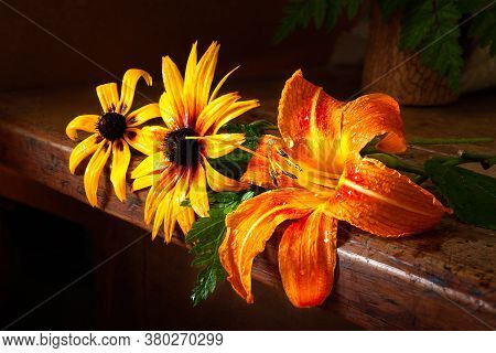 Daylily And Rudbeckia On A Wooden Table. Wet Flowers Of Day-lily And Rudbeckia In Drops Of Water On