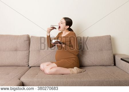 Hungry Pregnant Woman Is Eating A Piece Of Tasty Cake Relaxing On The Sofa At Home. Sweet Cravings D