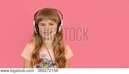 Little Girl In Headphones, Cheerfully Listens To Her Favorite Song. A Girl On A Pink Background List