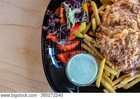 Top View Of A Dish In A Restaurant. Pork Chop With Fresh Vegetables And French Fries.