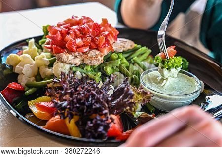 The Visitor In The Restaurant Eats Vegetables. Dips Vegetables Into Sauce.