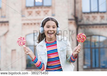 Cheerful Girl Modern Wireless Headphones Eat Candies, Confectionary Concept.