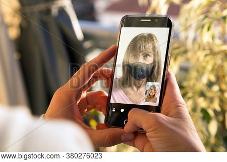 Two Women Talking To Each Other Through A Video Call On A Smartphone. Senior Woman With Medical Mask