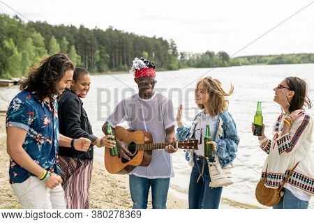 Group of positive young multi-ethnic friends dancing on beach under guitar music by hippie black guy