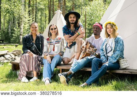 Group of smiling young multi-ethnic friends sitting on porch of camping tent and looking at camera while resting together