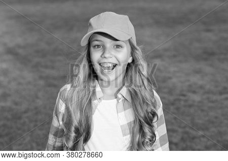 Young And Fun. Happy Child On Green Grass. Little Girl In Casual Style. Cool Casual Wear For Childre