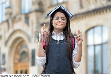 Crossing Fingers For Luck. Little Geek Make Wish Outdoors. Small Child Hold Book On Head. Knowledge