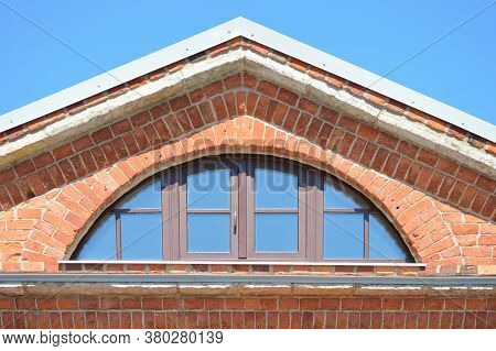 Big Semicircle Window In A Brick Pediment