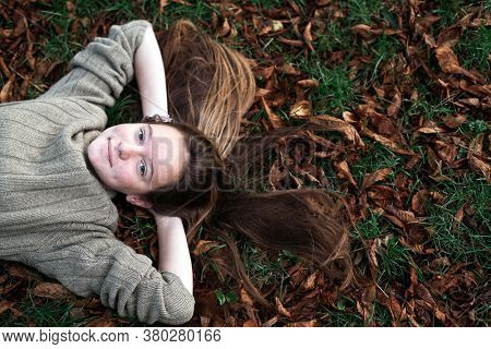 Teengirl laying on autumn ground with long hair scattered on grass.