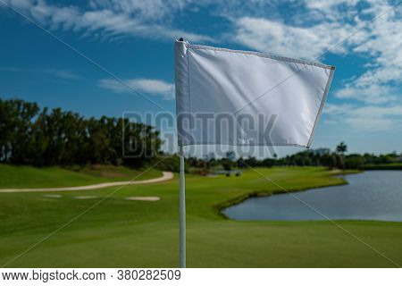 White Flag With A Place To Write. Countryside Golf Course With Flag, Greens And Water. Golf Course I