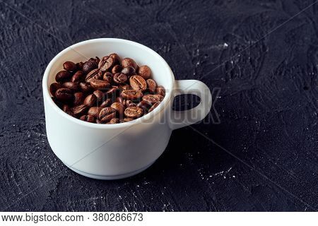 Roasted Whole Coffee Beans In White Porcelain Cup On Gray Textured Background