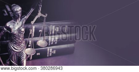 Scales of  justice and law books on desk.